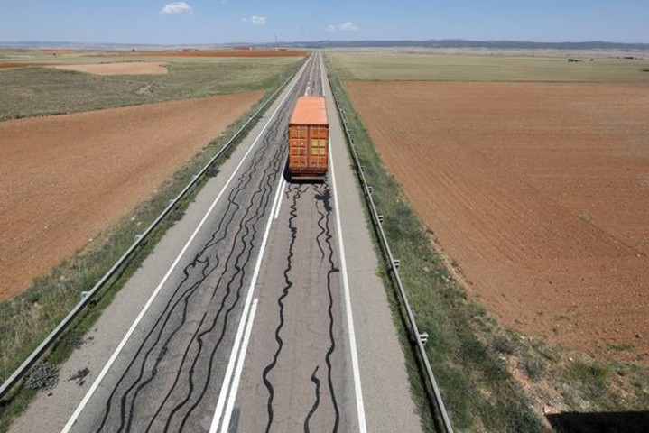 Las líneas de alquitrán y el motorista en la carretera