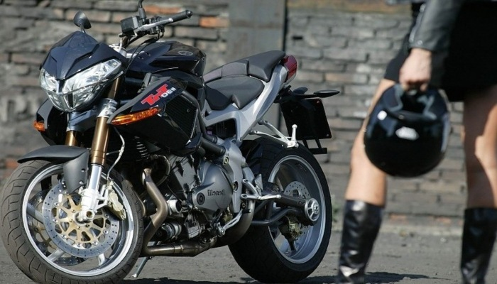hombre llevando casco hacia la moto