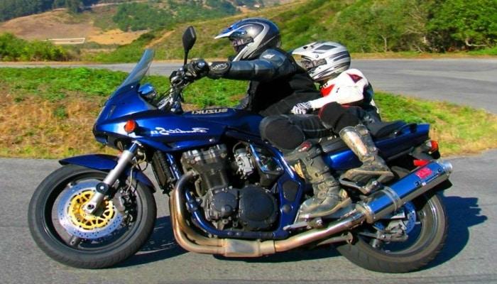 adulto llevando a niño por un prado con la moto