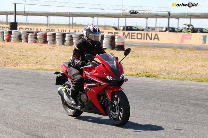Alumna en moto con tensión en los hombros.